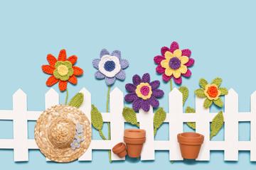 gehäkelte Blumen mit Zaun, Hut und Töpfen