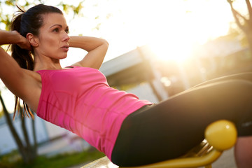 Woman sitting on bench outside doing situps.