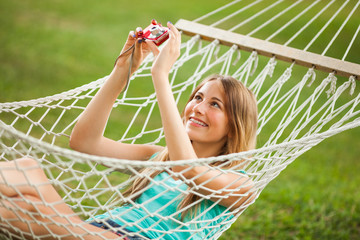 Happy girl laying in hammock and taking photo