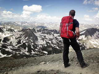 USA, Colorado, Man with backpack standing on trail, looking out at snowy mountains