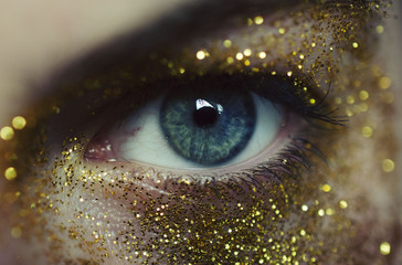 Close-up of woman eye with gold glitters