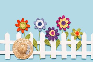 gehäkelte Blumen mit Gartenzaun und Hut