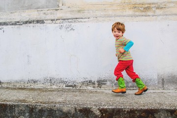 Boy (2-3) running against old wall