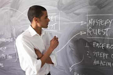 Businessman studying blackboard in office