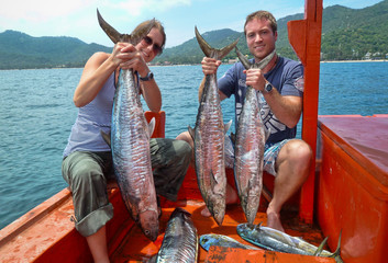 Thailand, Koh Tao, Mahi Mahi, Portrait of couple on boat holding catch of fish