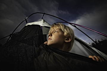 USA, Colorado, Boy (6-7) looking out of tent opening