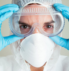 Close up of scientist putting on safety goggles