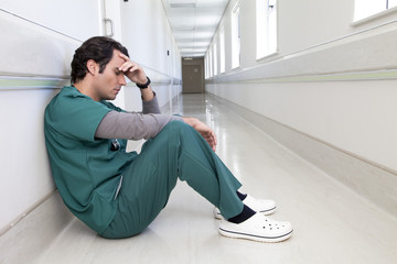 Tired doctor in hospital corridor