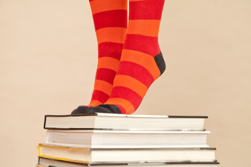 Feet in stripy socks, standing on pile of books