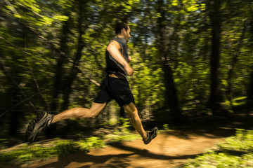 Athletic man running on trail through forest