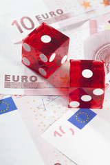 Two red dice on european banknotes