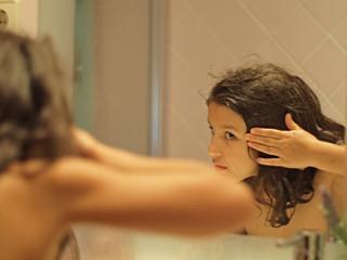 Spain, Barcelona, girl (8-9) looking at reflection in mirror, washing hair