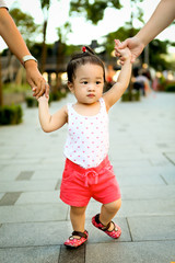 Girl (2-3) walking while adults hold her hands