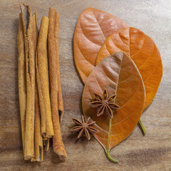 Still life of cinnamon sticks, anise cloves, and autumn leaves arranged on wooden surface
