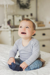 Netherlands, Smiling baby boy sitting on bed