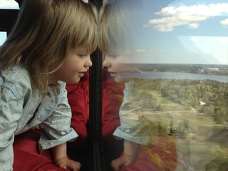 Stockholm, Sweden, A Young Boy Looking Out Through A Window, To See The View And Reflection