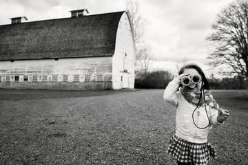 Young girl (2-3) looking through binoculars