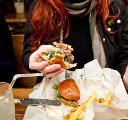 Woman eating hamburger, mid section