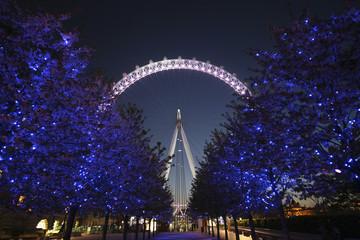 United Kingdom, England, London, Illuminated trees with London Eye on background at night