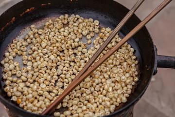 Vietnam, Hanoi, Vietnamese snack food being roasted in iron skillet with chopsticks