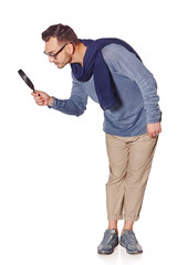 Serious man looking through magnifying glass