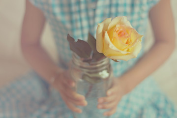 Girl in checked dress holding yellow rose in jar