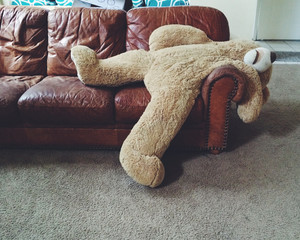 Stuffed teddy bear laying on couch