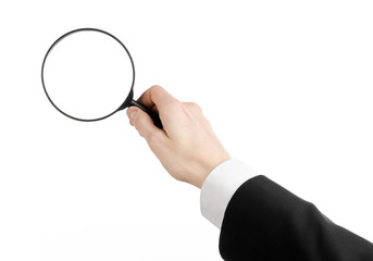 businessman in a black suit holding a magnifying glass