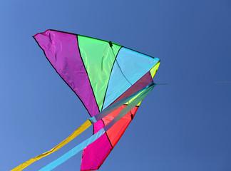huge kite flies high in the sky blue