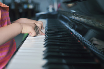 Close up of young girl (2-3) playing piano