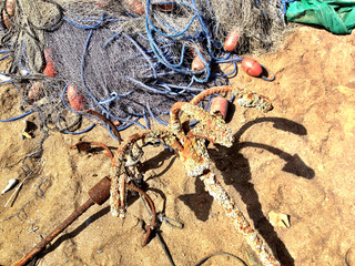 Oman, Muscat, Fishing net and anchors on beach
