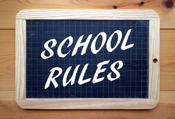 The phrase School Rules in white text on a blackboard