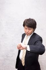 腕時計で時間を確認するアジアのビジネスマン