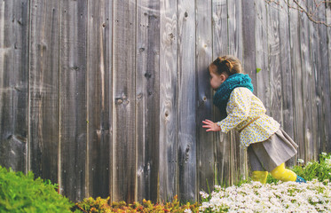 Girl (2-3) looking trough wooden fence