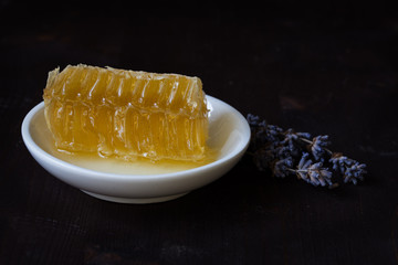 Piece of honey comb on plate and lavender, against black background