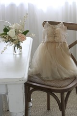 Child's ballet dress on chair next to vase of roses