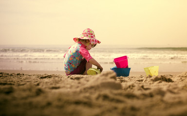 Girl (18-23 months) playing in sand on beach