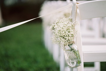 USA, Florida, Orange County, Winter Park, Close-up shot of bunch of baby's breath flowers in a mason jar and white ribbon attached to back of white chair