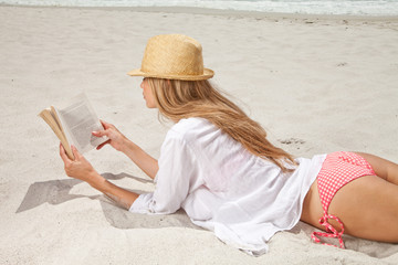 South Africa, Young woman lying down on beach reading a book