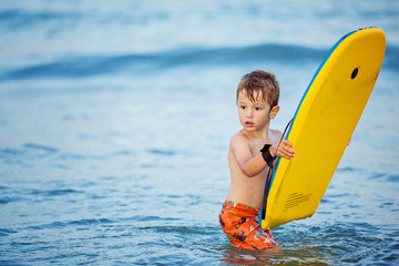 Boy (2-3) standing in sea with surfboard