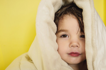 Boy (2-3) wrapped in towel against yellow