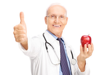 Mature doctor holding apple and giving thumb up