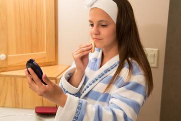 Young girl (12-13) applying make-up