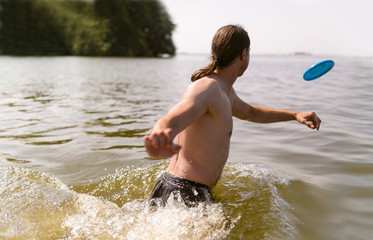 The Netherlands, Jsselmeer, Man in lake playing with plastic flying disc