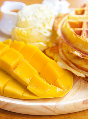 Mango with waffle and ice cream on wooden board