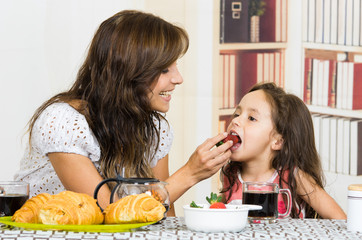 Beautiful young mom feeding fruit to cute little girl