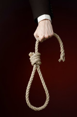 Hand of a businessman holding a loop of rope for hanging