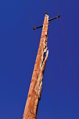 USA, Arizona, Wooden electricity post against blue sky