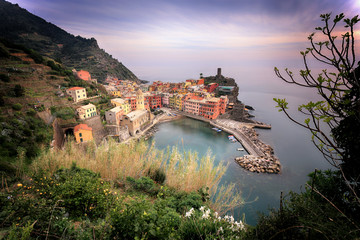 Italy, Liguria, Vernazza, Elevated view of seaside village at sunset