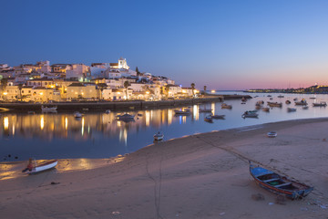 Portugal, Algarve, Ferragudo, Illuminated town and boats in harbor